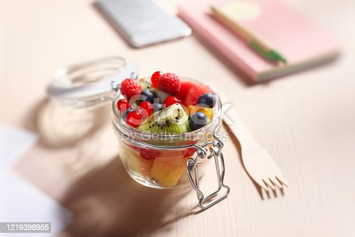 Fruits salad in a glass container with wooden fork in the office.