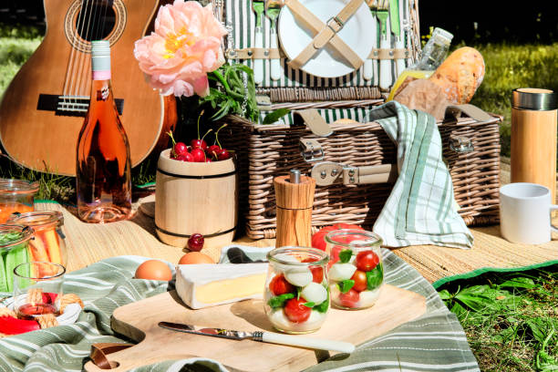 Zero waste picnic al fresco. Vintage picnic basket, hamper with baguette and lemonade outdoors on a grass with cheese, mozzarella, tomatoes, cherries, vine. Guitar on straw blanket and stripy towels. stock photo