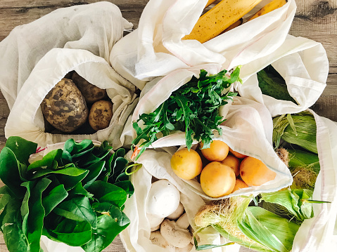 istock zero waste shopping concept. fresh vegetables in eco cotton bags on table in the kitchen. lettuce, corn, potatoes, apricots, bananas, rucola, mushrooms from market.  ban plastic 1034981386