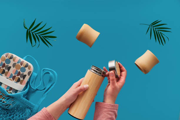 Zero waste tea in in eco friendly insulated bamboo flask. Two hands with cup and palm leaf, net bag with lunch box and tea flask are flying.Zero waste concept levitation on cyan, blue mint background. stock photo