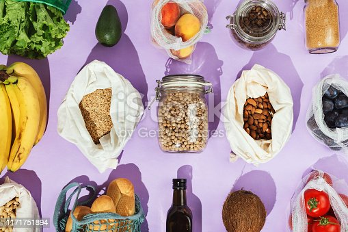 Zero-waste healthy grocery shopping concept:  pulses, fruits, greens and vegetables in mesh net or cotton bags and glass jars