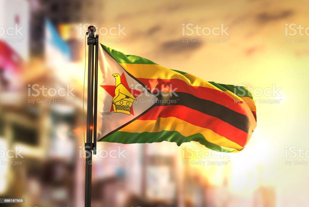 Zimbabwe Flag Against City Blurred Background At Sunrise Backlight stock photo