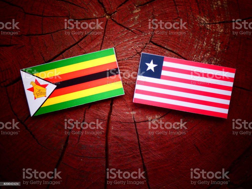 Zimbabwe flag with Liberian flag on a tree stump isolated stock photo