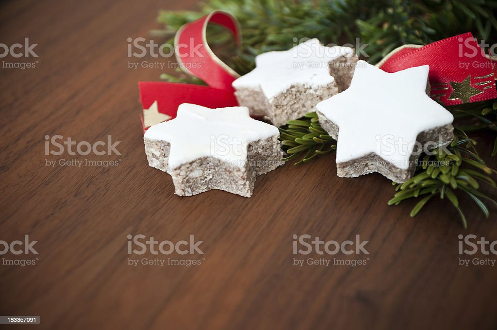 Zimtstern cookies on walnut table with fir branches royalty-free stock photo