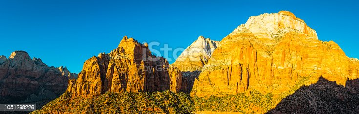 Warm early morning sunlight illuminating the golden canyon walls, slickrock mesas and cottonwood tree valleys of Zion National Park, Utah, USA.