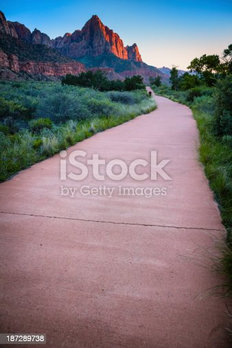 The Pa'rus Trail in Zion National Park, Utah, at dusk. A mostly flat paved trail suitable for wheelchairs, cycling and easy walking. In the distance is the distinctive peak of The Watchman.