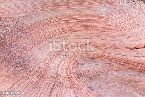Zion National Park in Utah on Gifford Canyon trail with red pink sandstone layers wave formation on rock wall cliff abstract closeup of design