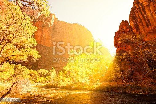 Photo of a river with sunlight coming from behind a mountain, at Zion National Park.