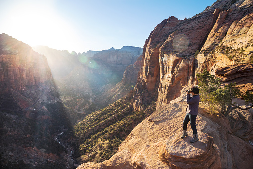 mature woman taking a picture of the sunset at lookout point in Zion National Park
