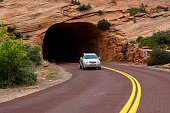 Springdale, Utah, USA - May 23, 2014: People in a car coming out of a tunnel on a road through the rugged and beautiful landscape of Zion National Park near Springdale, Utah.