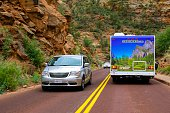 Springdale, Utah, USA - May 23, 2014: People and traffic on a road through the rugged and beautiful landscape of Zion National Park near Springdale, Utah.