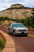 Springdale, Utah, USA - May 23, 2014: People in a car on a road through the rugged and beautiful landscape of Zion National Park near Springdale, Utah.