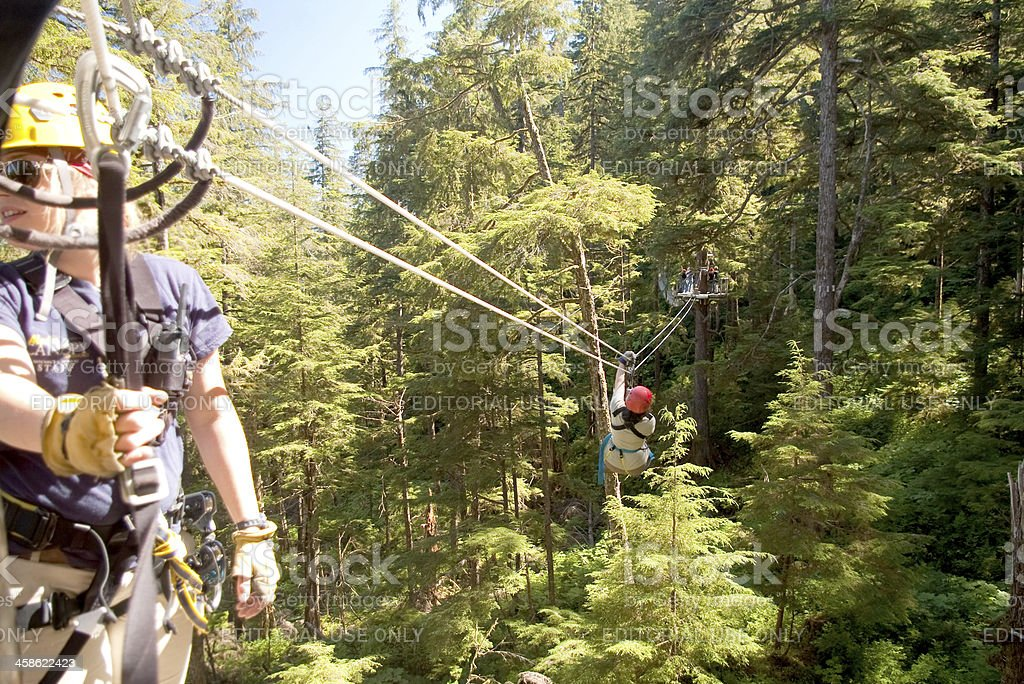 """Zip Line """"Ketchikan, USA - August 12, 2010. A female zip line attendant awaits the next adventurer at the Alaskan Canopy Adventures, a popular excursion for the many cruise ships that dock there. A mature woman zips into the background."""" Adult Stock Photo"""