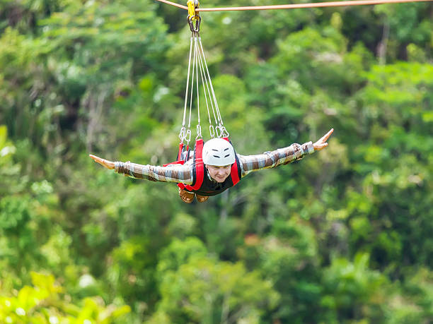 Zip-line Men enjoying zip-line flying over the forest zip line stock pictures, royalty-free photos & images