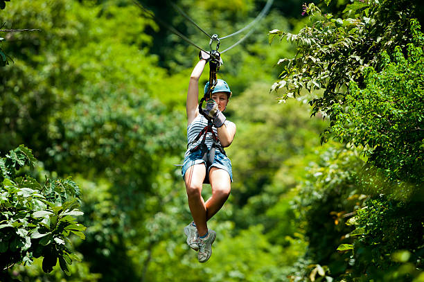 Ziplining in Costa Rica A girl is photographed sliding down an aerial steel cable (zipwire) at high speed in the rainforest in Costa Rica. canopy stock pictures, royalty-free photos & images
