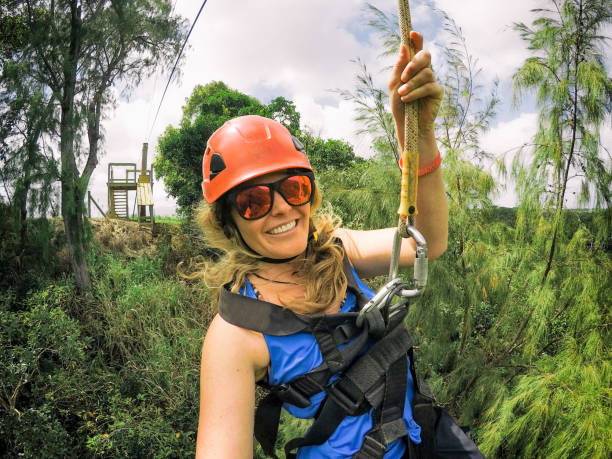 Ziplining Mama in the Jungle Woman in her 30s zip-lines in a tropical jungle while on vacation. Beautiful views and happy smiles in Kauai, Hawaii. zip line stock pictures, royalty-free photos & images