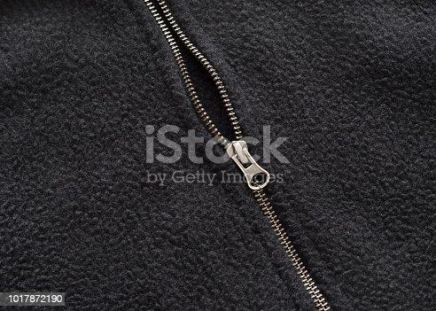 Closeup of a zipper on a black fleece coat.