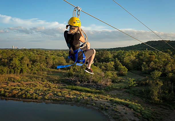 Zipping Fun Girl Young woman riding a Zipline Canopy Tour zip line stock pictures, royalty-free photos & images