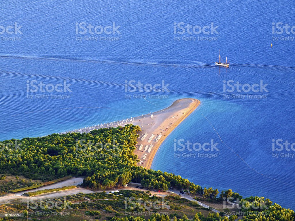 Zlatni rat The Golden Cape (Zlatni rat) beach on island Brac, Croatia. It is triangle of shingle that changes shape with the winds and tides with perfect azure sea. It is surfing meca. Balkans Stock Photo