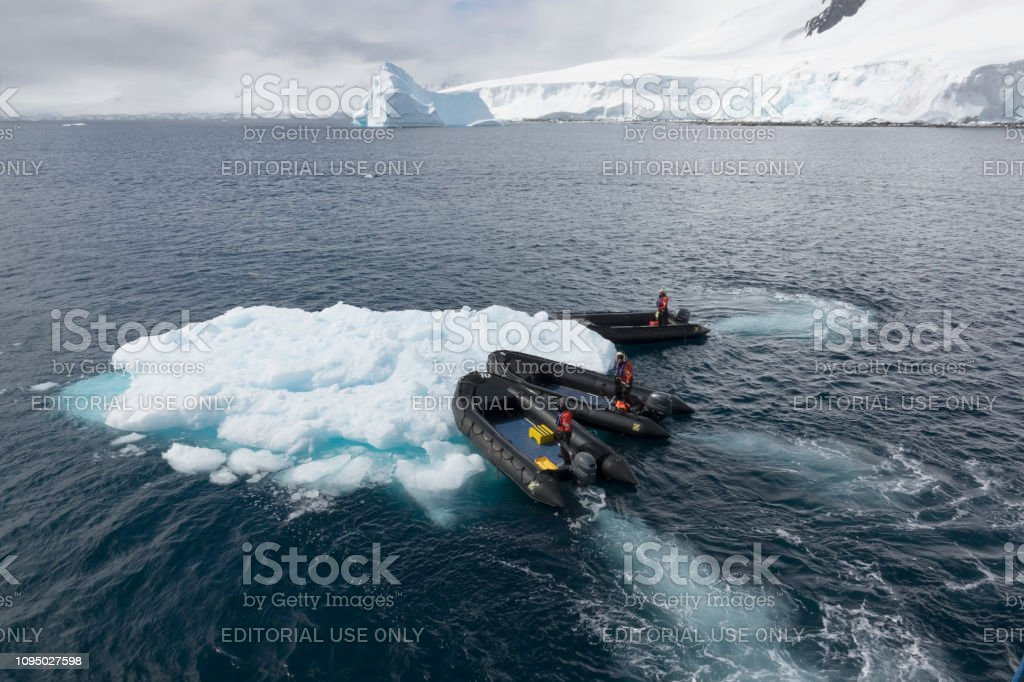 Zodiac expedition guides push iceberg Damoy Point Wiencke Island Antarctic Peninsula Antarctica stock photo