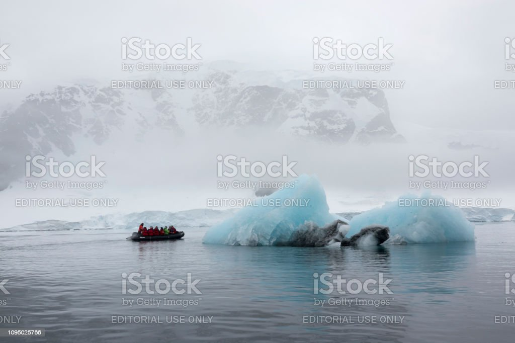 Zodiac motorboat carries travelers Danco Island glacier iceberg Antarctica Gerlache Strait Antarctica stock photo