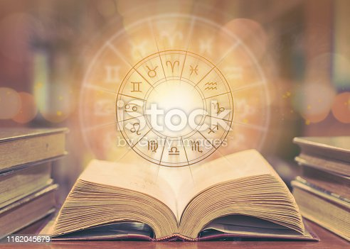 istock Zodiac sign horoscope astrology and constellation study for foretell and fortune telling education course concept with horoscopic wheel over old book in school library 1162045679