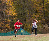 Indiana, USA - October 31, 2015: A female zombie chases a panicked male athlete running across grass as they participate in the 5K Zombie Run at USI in Evansville