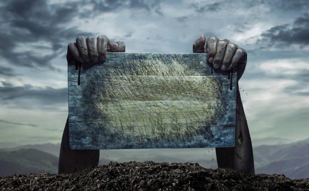 Zombie-Hand hält alte Holzbrett, leeren Raum für Text oder Zeichnen – Foto