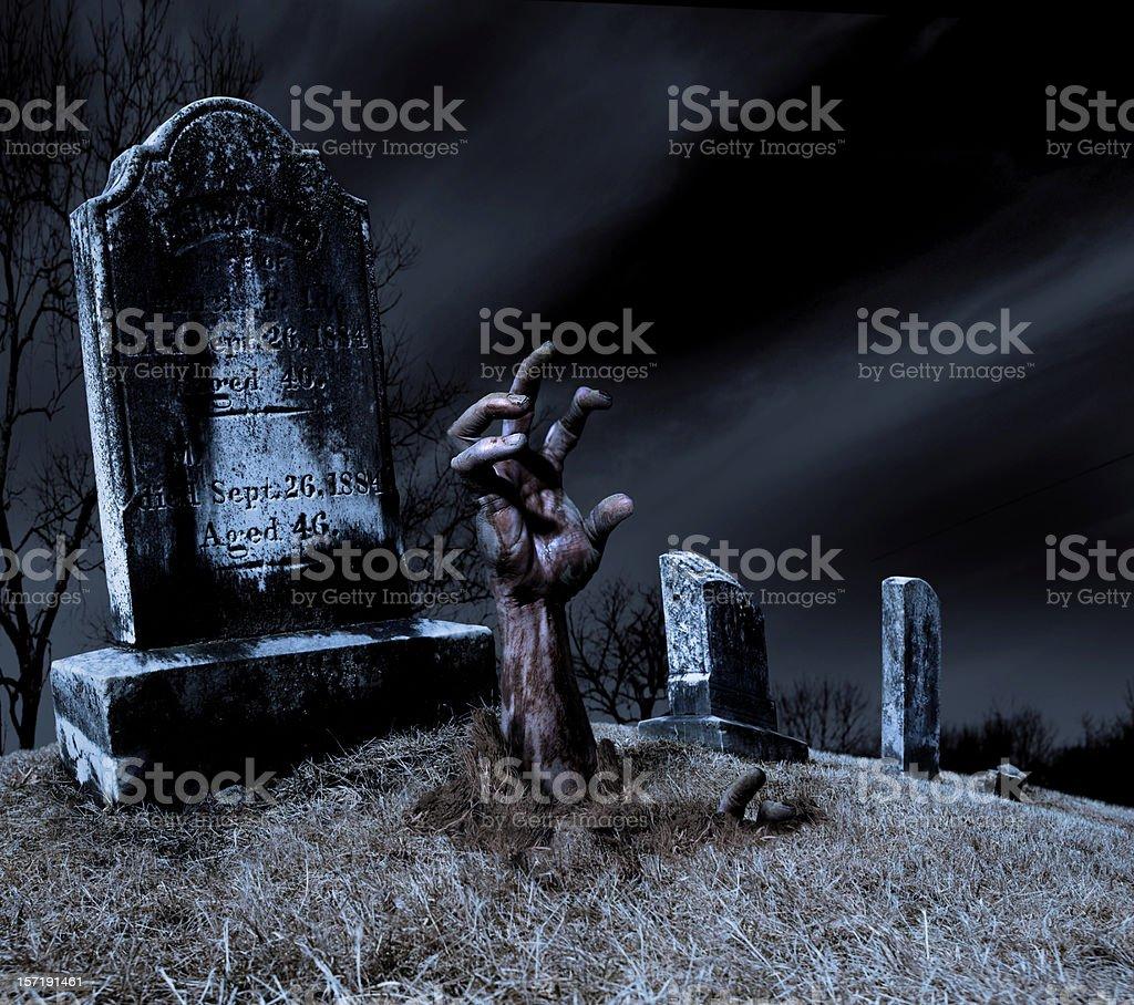 Zombie hand rising out of a grave stock photo