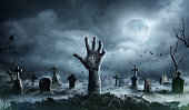 istock Zombie Hand Rising Out Of A Graveyard In Spooky Night 1031484946