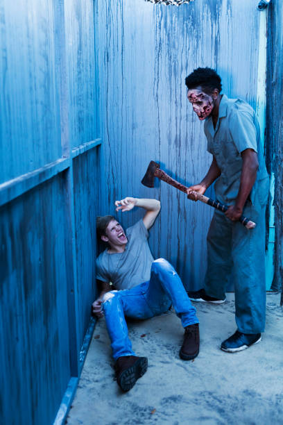 Zombie in haunted house standing over victim with axe stock photo