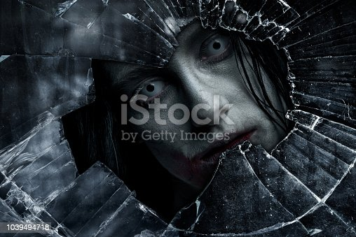 Zombie looking through old window. Halloween theme.