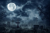 Zombie Rising Out Of A Graveyard cemetery In Spooky dark Night full moon. Holiday event halloween concept.