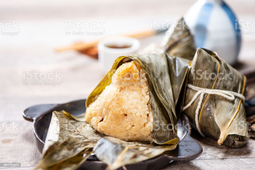 zongzi(rice dumpling) with a cup of tea on a wood table, Dragon Boat Festival, Asian traditional food, Chinese royalty-free stock photo