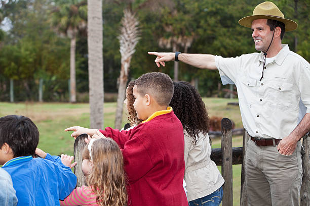 Zoo keeper with group of children at animal exhibit Zoo keeper (30s) with multi-ethnic group of elementary school children at zoo, standing on observation deck overlooking animal exhibit. park ranger stock pictures, royalty-free photos & images
