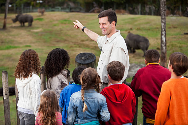 zoowärter mit gruppe von kindern im rhino ausstellung - vorschulzoothema stock-fotos und bilder