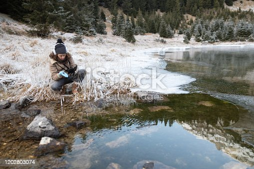 Zoologist Examining Lake Life in Winter.