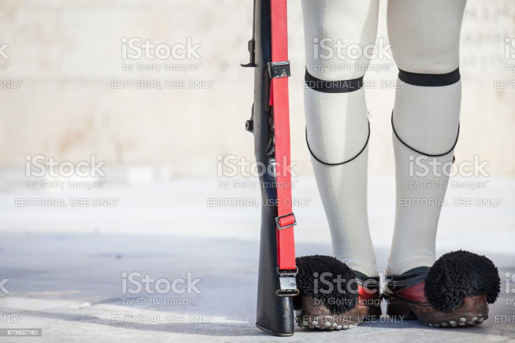 Zoom on the shoes and rifle of Evzones, the Greek presidential guard, in front of the Greek parliament on Syntagma square. The Evzoni are one of the symbols of Greece stock photo