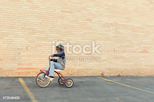A young African American boy zips through the city on his tricycle.
