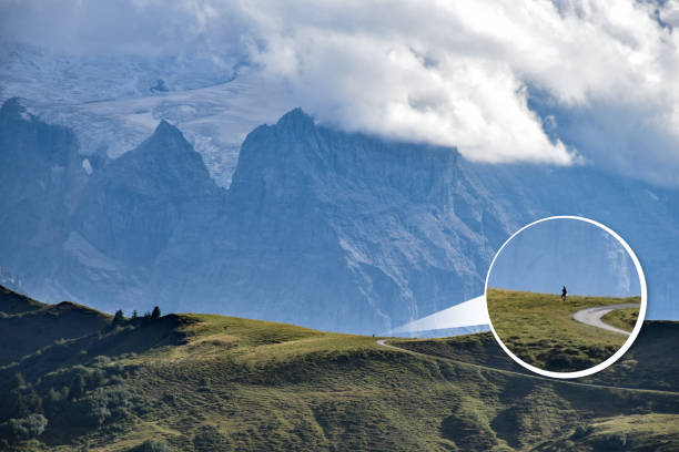 A zoomed-in balloon of a tiny hiker as opposed to the huge mountain range in the background, creating a sense of humility and scale stock photo