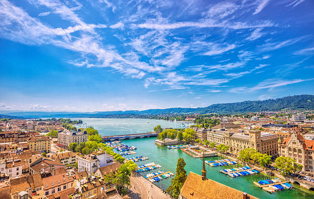 Zürich, Lake Zurich and Swiss Alps Elevated view over the old town of Zurich with the  Stadthausquai and traditional public Limmat river bath (Frauenbad), the lake Zurich and the Swiss alps in the distance on a beautiful summer day. zurich stock pictures, royalty-free photos & images