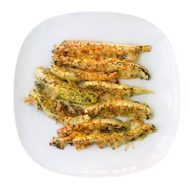 zucchini gebacken mit käse und kräutern auf weißen teller. appetitlich zucchini in form von sticks.  vegetarische küche. gemüse-kurs. - käse zucchini backen stock-fotos und bilder