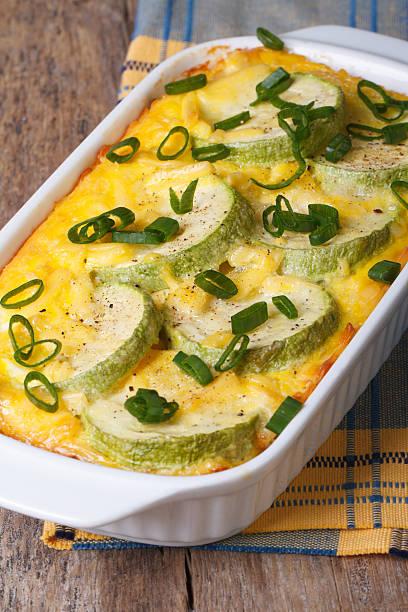 gebackener zucchini mit käse, eiern und zwiebeln vertikal - käse zucchini backen stock-fotos und bilder
