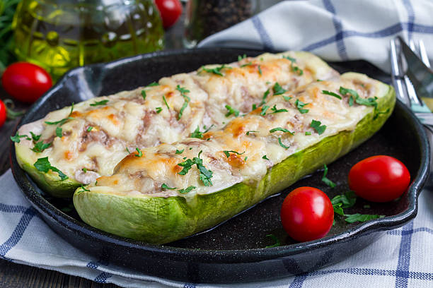 zucchini boats stuffed with ground meet and topped with cheese - käse zucchini backen stock-fotos und bilder