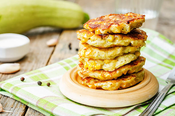 zucchini corn fritters zucchini corn fritters on a dark wood background. the toning. selective focus fritter stock pictures, royalty-free photos & images