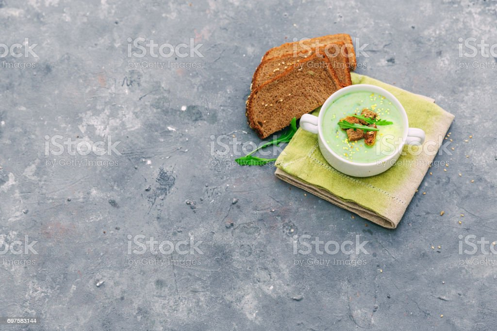 Zucchini creamy soup with basil on a light background. stock photo