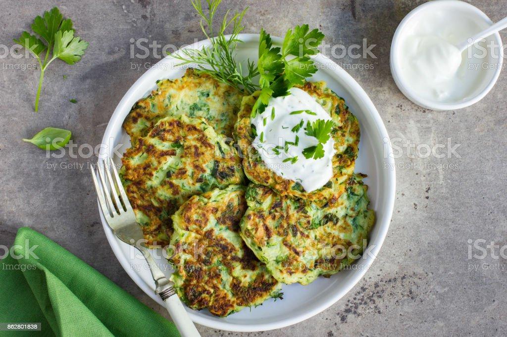 zucchini fritters, vegetarian zucchini pancakes, served with fresh herbs and garlic yogurt sauce - Foto stock royalty-free di Aglio - Alliacee