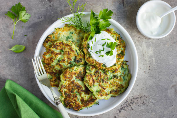 zucchini fritters, vegetarian zucchini pancakes, served with fresh herbs and garlic yogurt sauce zucchini fritters, vegetarian zucchini pancakes, served with fresh herbs and garlic yogurt sauce, top view fritter stock pictures, royalty-free photos & images