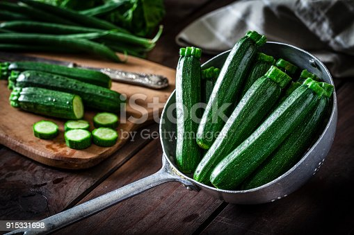 Fresh organic zucchini in an old metal colander shot on rustic wooden table. This vegetable is considered a healthy salad ingredient. Predominant colors are green and brown. Low key DSRL studio photo taken with Canon EOS 5D Mk II and Canon EF 100mm f/2.8L Macro IS USM
