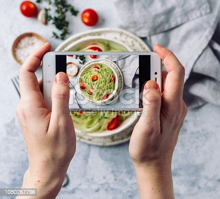Woman hands takes top view photography of zucchini noodles salad on table with phone. Smartphone photo for social networks or blogging post.Vegetarian, healthy, organic, clean eating, raw food concept